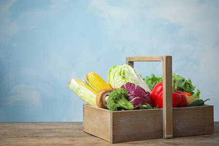 Different fresh vegetables in crate on wooden table