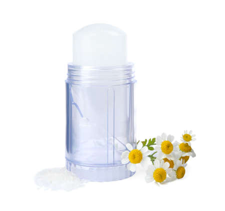 Natural crystal alum deodorant with chamomile flowers on white background