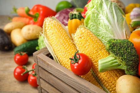 Fresh vegetables and wooden crate on table, closeup 写真素材