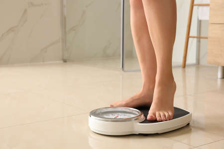 Woman standing on scales in bathroom, space for text. Overweight problem