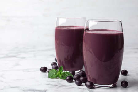 Tasty acai drink in glasses and berries on marble table 写真素材
