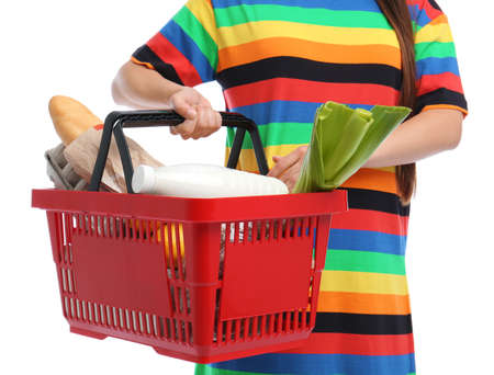 Young woman with shopping basket full of products isolated on white, closeup