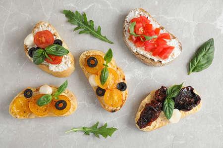 Delicious tomato bruschettas on light grey marble background, flat lay Banco de Imagens