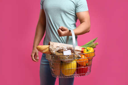 Young man with shopping basket full of products on pink background, closeup