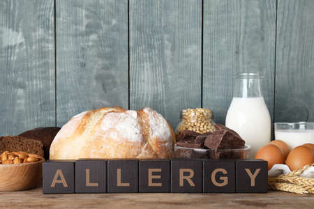 Different products on wooden background. Food allergy concept