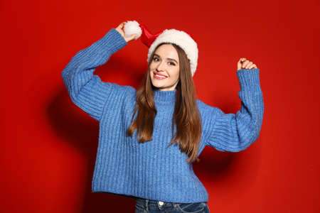 Young woman in Christmas sweater and Santa hat on red background Stock Photo