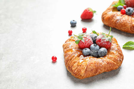 Fresh delicious puff pastry with sweet berries on light background. Space for text