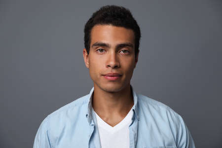 Handsome young African-American man on grey background