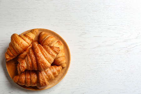Plate with tasty croissants and space for text on white wooden background, top view. French pastry