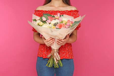 Young woman holding beautiful flower bouquet on pink background, closeup Stockfoto