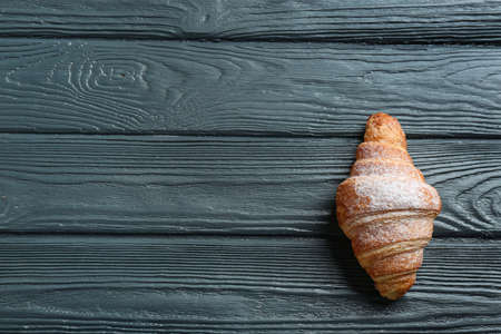 Tasty croissant with powdered sugar and space for text on dark wooden background, top view. French pastry