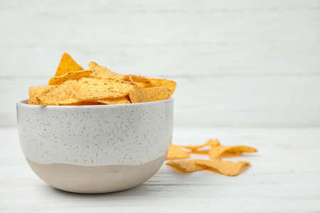 Bowl with tasty Mexican nachos chips on white wooden table, space for text