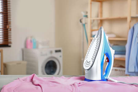Modern electric iron and clean shirt on board in laundry room. Space for text Imagens