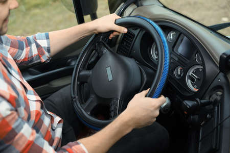 Mature driver sitting in cab of modern truck, closeup view