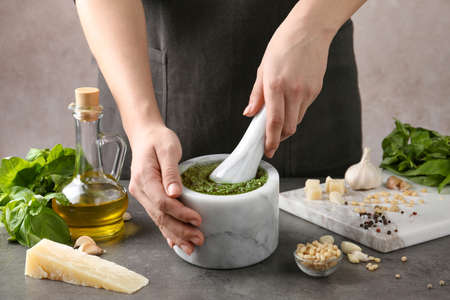 Woman mashing pesto sauce in mortar at table, closeup