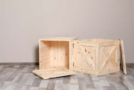 Wooden crates on floor at beige wall. Space for text