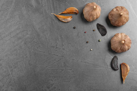 Flat lay composition with black garlic and space for text on grey background Archivio Fotografico