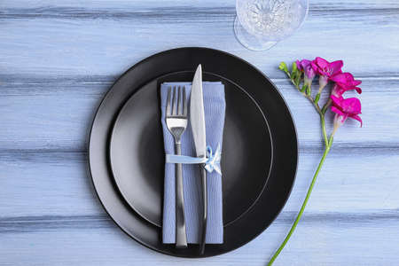 Stylish elegant table setting with freesia on blue wooden background, top view