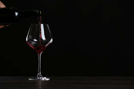 Woman pouring wine into glass on table against black background, closeup with space for text Stok Fotoğraf