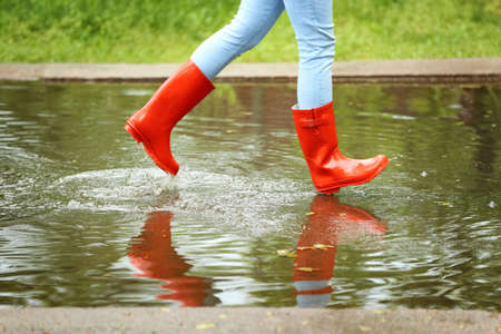 Woman with red rubber boots running in puddle, closeup. Rainy weather