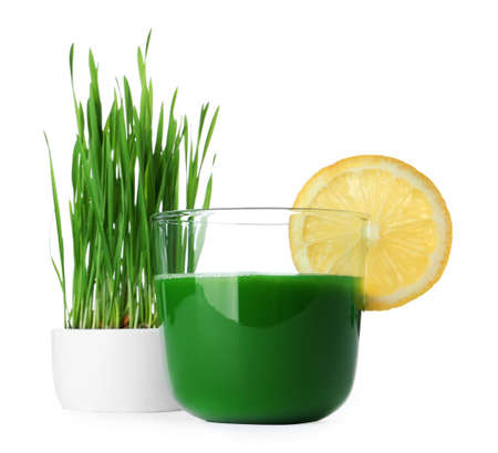 Glass of wheat grass juice served with slice of lemon and sprouts on white background