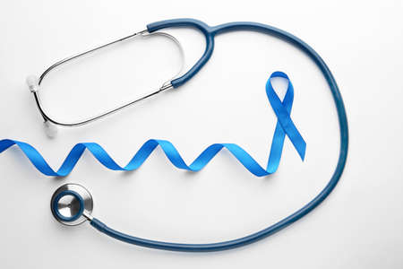 Blue awareness ribbon and stethoscope isolated on white, top view. Symbol of medical issues