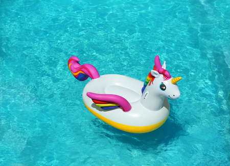 Funny inflatable unicorn ring floating in swimming pool on sunny day. Space for text 版權商用圖片 - 128776205