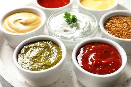 Set of different delicious sauces on tray, closeup