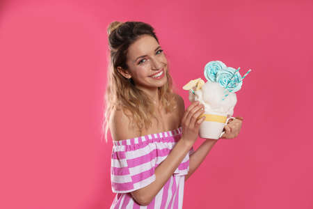 Portrait of young woman holding cotton candy dessert on color background Stock Photo