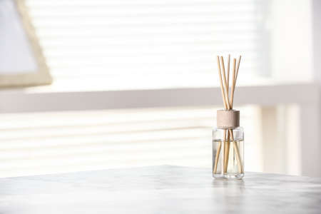 Aromatic reed air perfume on white table at home, space for text