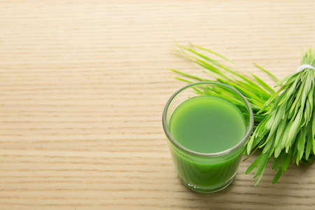 Shot glass of wheat grass juice and sprouts on wooden table, space for text