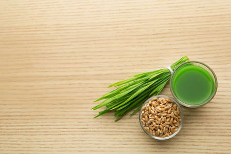 Shot glass of wheat grass juice, bowl with grains and sprouts on wooden table, flat lay. Space for text