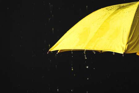 Opened yellow umbrella under rain against black background, closeup