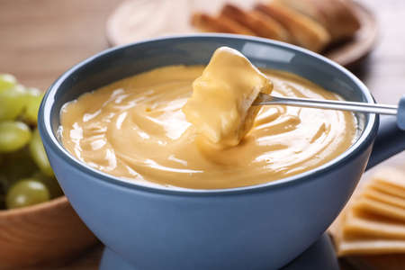 Dipping bread into pot with cheese fondue on table, closeup Banque d'images
