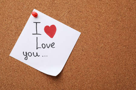 Paper sheet with words I LOVE YOU and heart on cork background, top view. Space for text Stock fotó