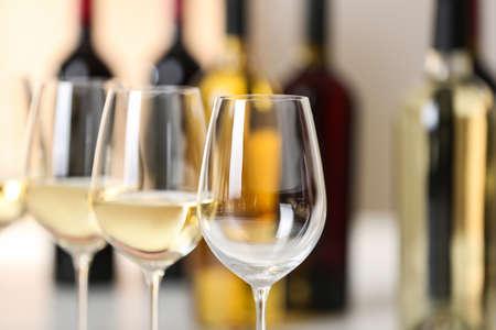 Rij wijnglazen en wazige flessen op de achtergrond, ruimte voor tekst Stockfoto