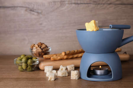 Pot of cheese fondue and products on wooden table, space for text Banque d'images