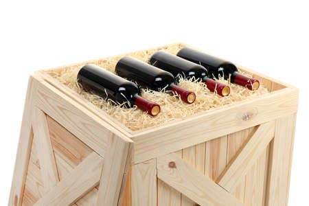 Bottles of wine in open wooden crate isolated on white