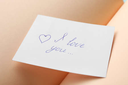 Paper sheet with words I LOVE YOU on open notebook, closeup