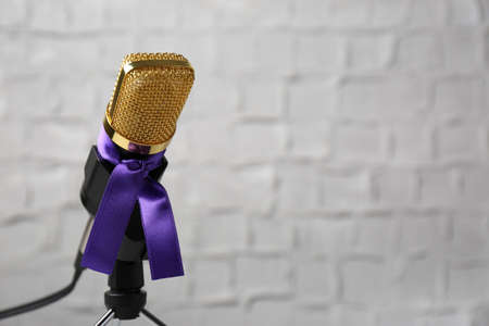 Microphone with purple awareness ribbon against white wall, space for text