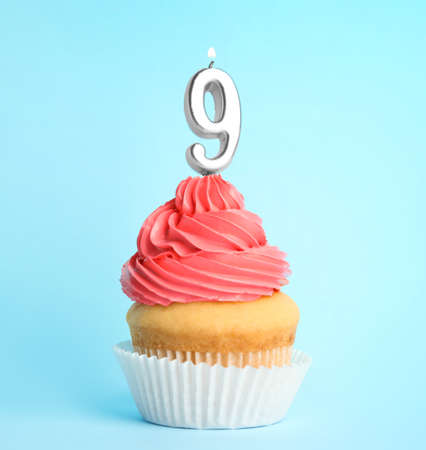 Birthday cupcake with number nine candle on blue background Stock fotó