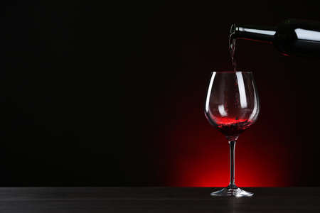 Pouring wine from bottle into glass on table against dark background, space for text