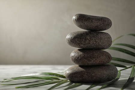 Stack of spa stones and palm leaf on grey table, space for text