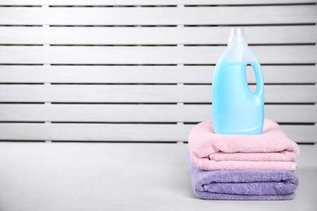 Clean towels and bottle of laundry detergent on table against blurred background. Space for text 版權商用圖片
