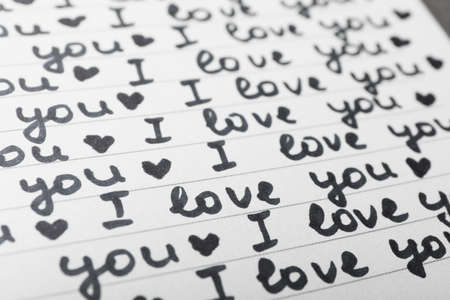 Notebook page with words I LOVE YOU and hearts as background, closeup