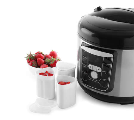 Modern multi cooker with cups of homemade yogurt and strawberries isolated on white Stock Photo