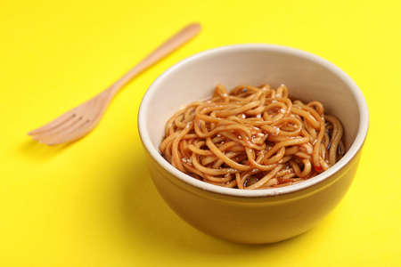 Cooked noodles and wooden fork on yellow background