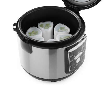 Open multi cooker with cups of homemade yogurt isolated on white