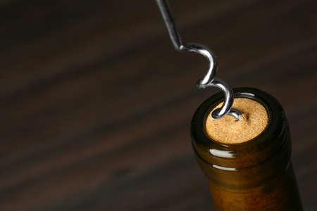 Bottle of wine and corkscrew on dark background, space for text