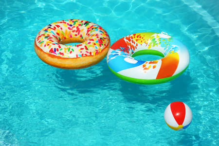 Bright inflatable rings and beach ball floating in swimming pool on sunny day. Space for text 版權商用圖片 - 128771522